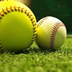 Baseball and softball laying on the grass